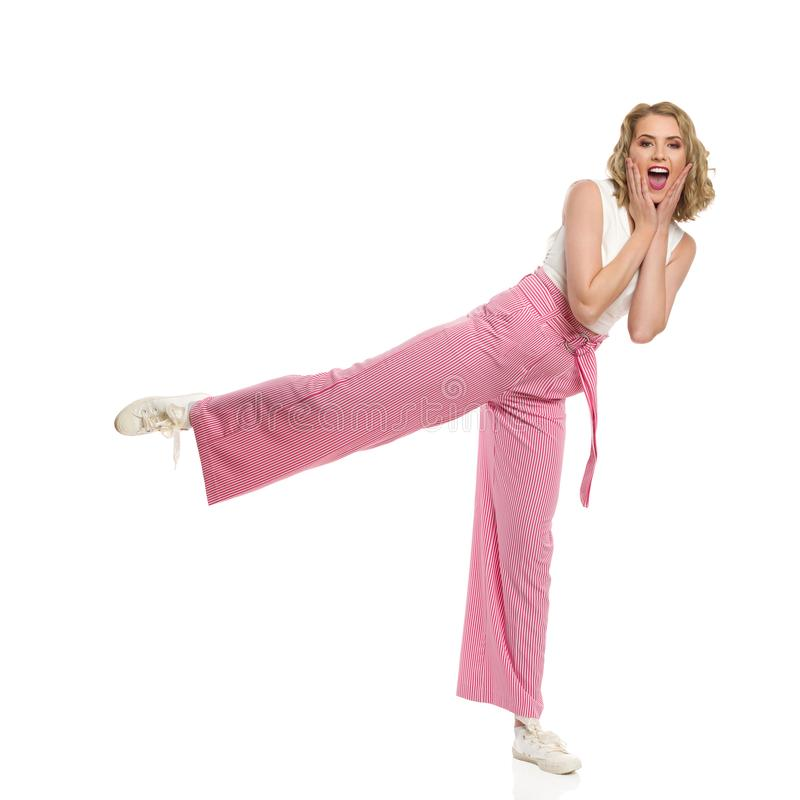 Excited Woman In Striped Wide Legs Trousers Is Standing On One Leg And Holding Head In Hands. Excited young woman in striped wide legs trousers is standing on stock photo