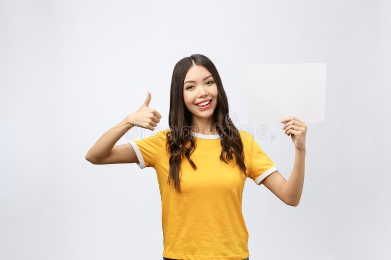 Excited woman thumbs up with blank poster sign. Young woman mixed asian caucasian ethnicity. stock images