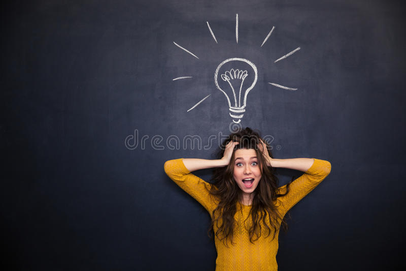Excited woman with tousled hair standing over blackboard background. Excited pretty young woman with tousled hair and hands on head standing over blackboard stock image