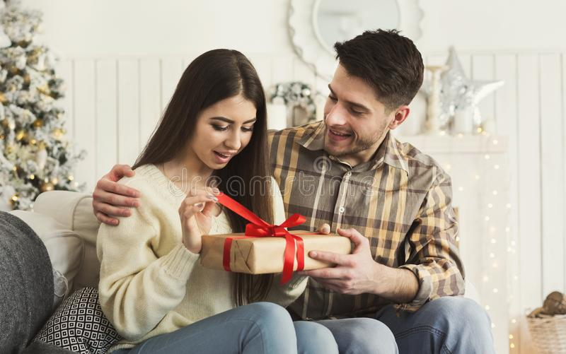 Handsome man surprising girl with Christmas gift. Excited women opening Christmas gift from her boyfriend at home, copy space stock image