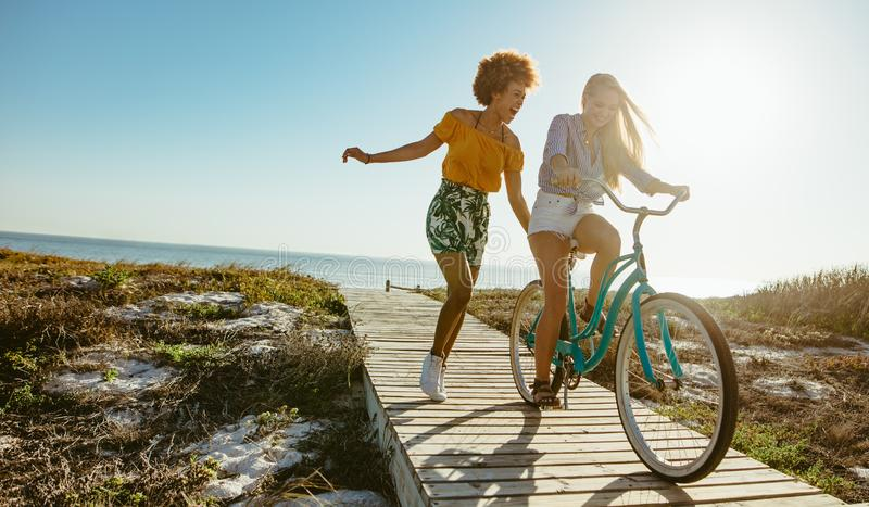 Friends enjoying themselves with a bicycle stock photo