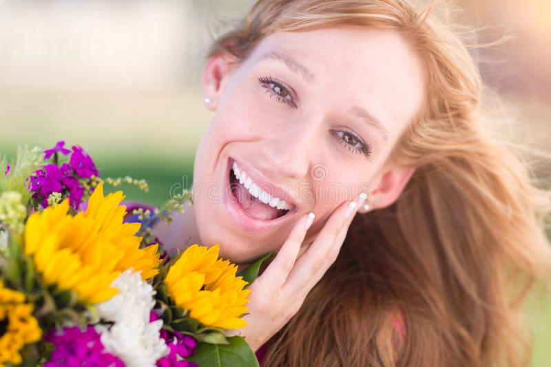 Excited Young Adult Brown Eyed Woman Holding Bouquet of Flowers. Outdoor Portrait of an Excited Young Adult Brown Eyed Woman Holding a Bouquet of Flowers stock image