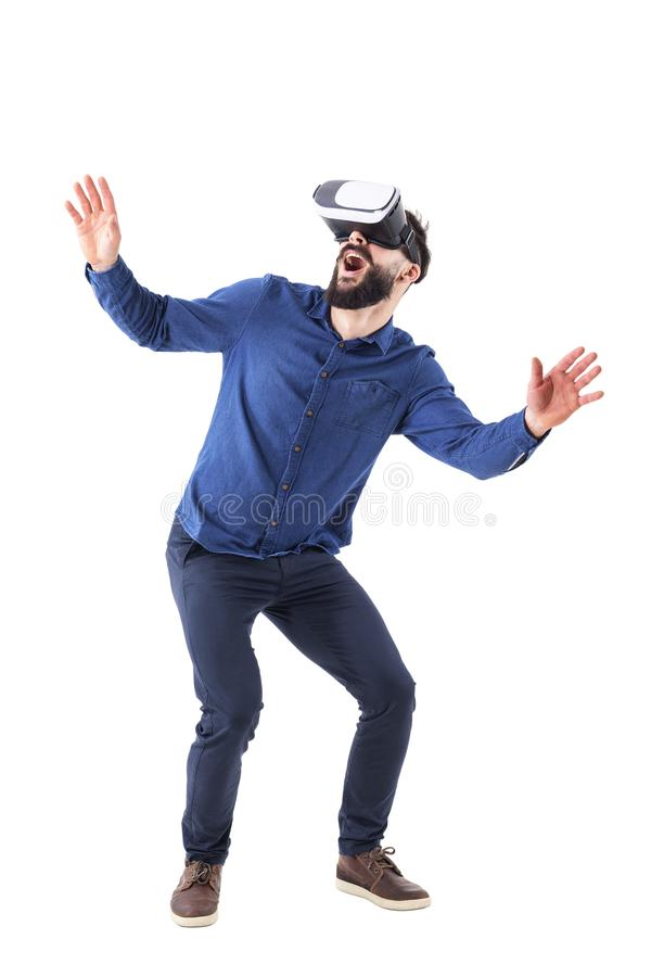 Excited young adult man bending and crouching having virtual reality glasses experience. Full body isolated on white background stock image