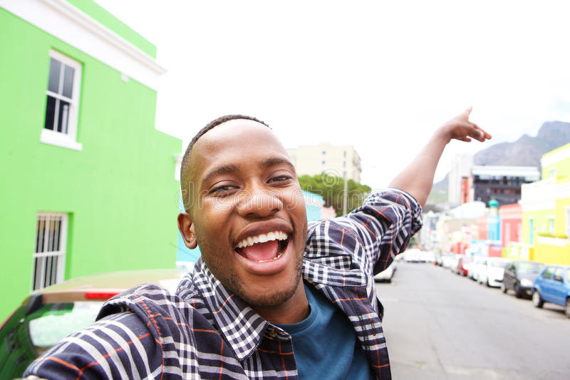 Excited young african guy taking a selfie. Close up of excited young african guy out on the city street taking a self portrait royalty free stock photography