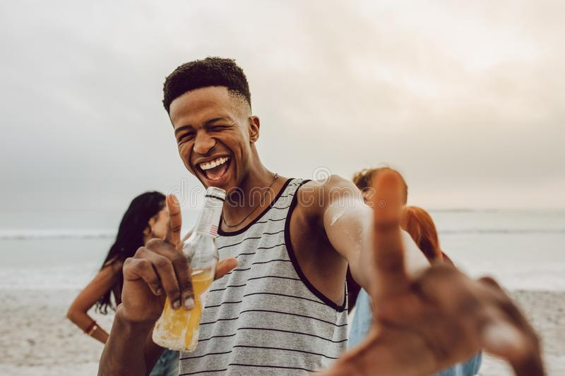 Man enjoying at the beach. Excited young african men with beer on the beach with friends at the back. Smiling male with group of friends in background at beach stock images