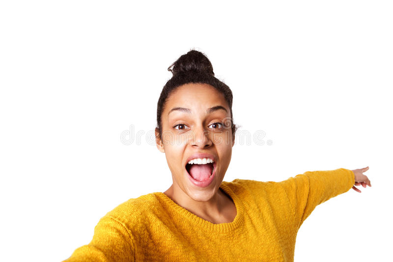 Excited young african woman pointing back and taking selfie. Close up portrait of excited young african woman pointing back and taking selfie on white background royalty free stock photos