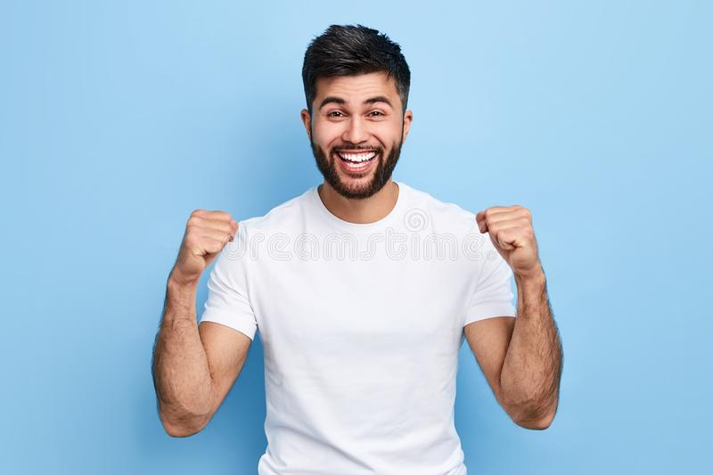 Excited young Arab man celebrating success, victory stock images