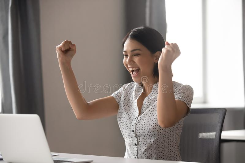 Excited young asian business woman celebrating successful financial project results. royalty free stock photo