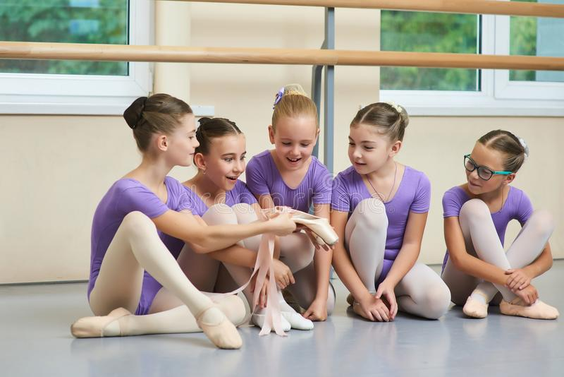 Excited young ballerinas looking on new slippers. Beautiful young ballerina showing new ballet shoes to her friends. Childrens expression of excitement royalty free stock image