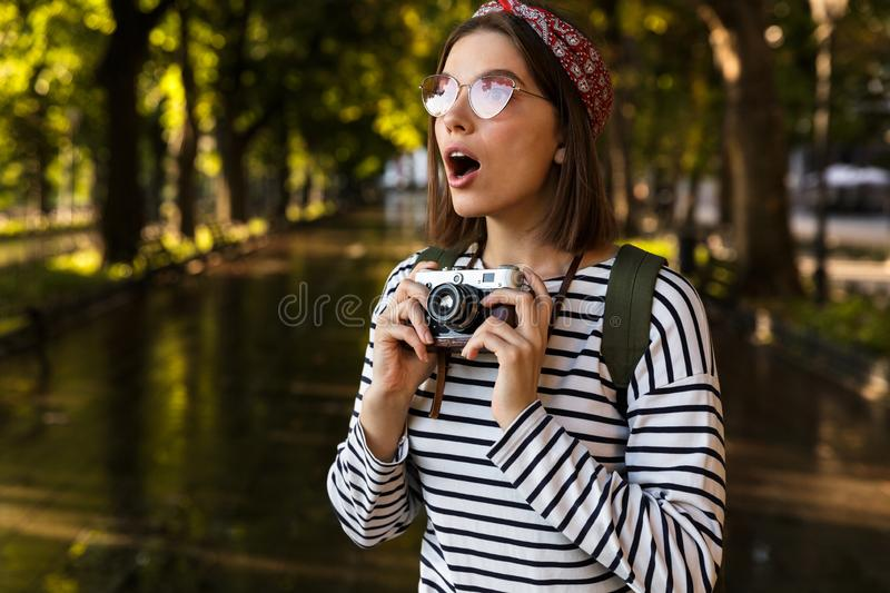 Excited young beautiful woman walking outdoors with camera. royalty free stock photography