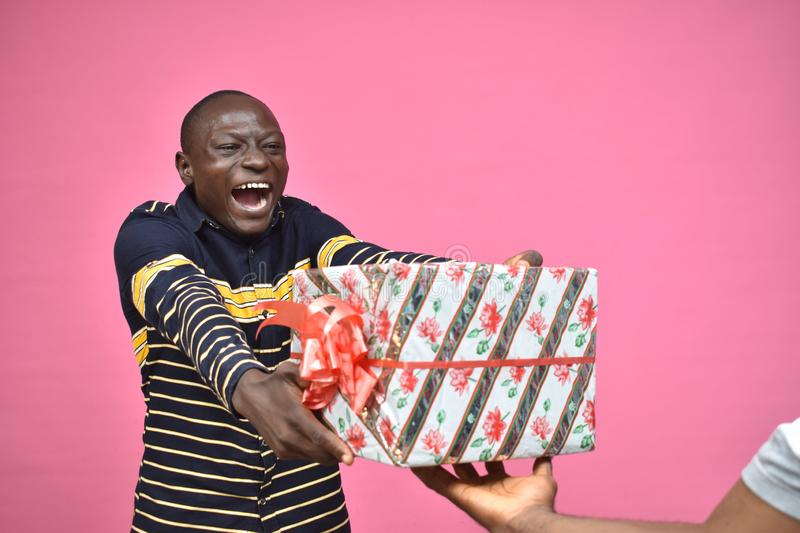 excited young black man feeling super excited receiving a present from someone royalty free stock photography