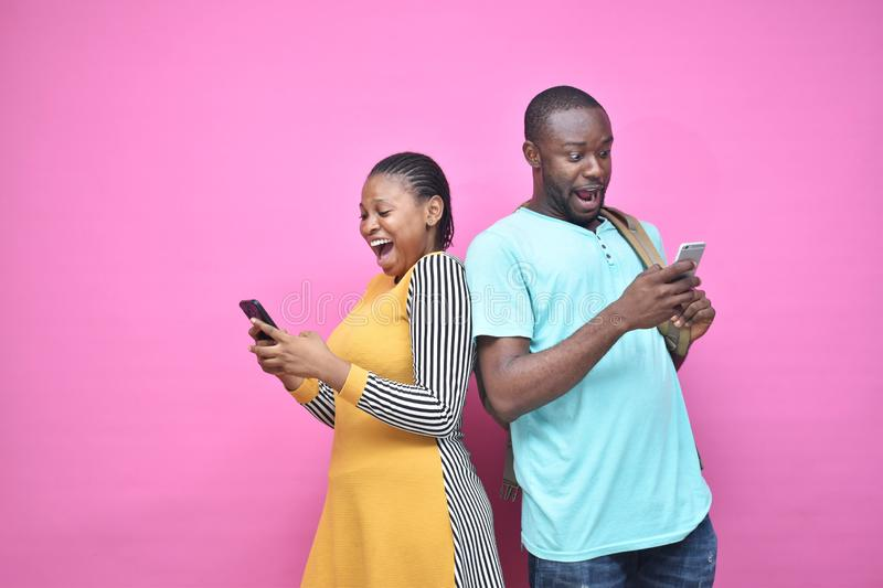 excited young black people standing back to back viewing contents on their phones, looking surprised, young african man and woman stock photo