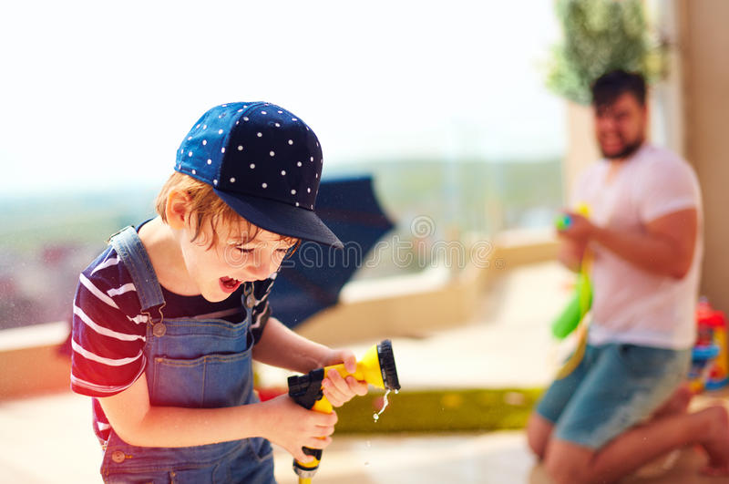 Excited young boy having fun, splashing water with father at warm summer day stock photo