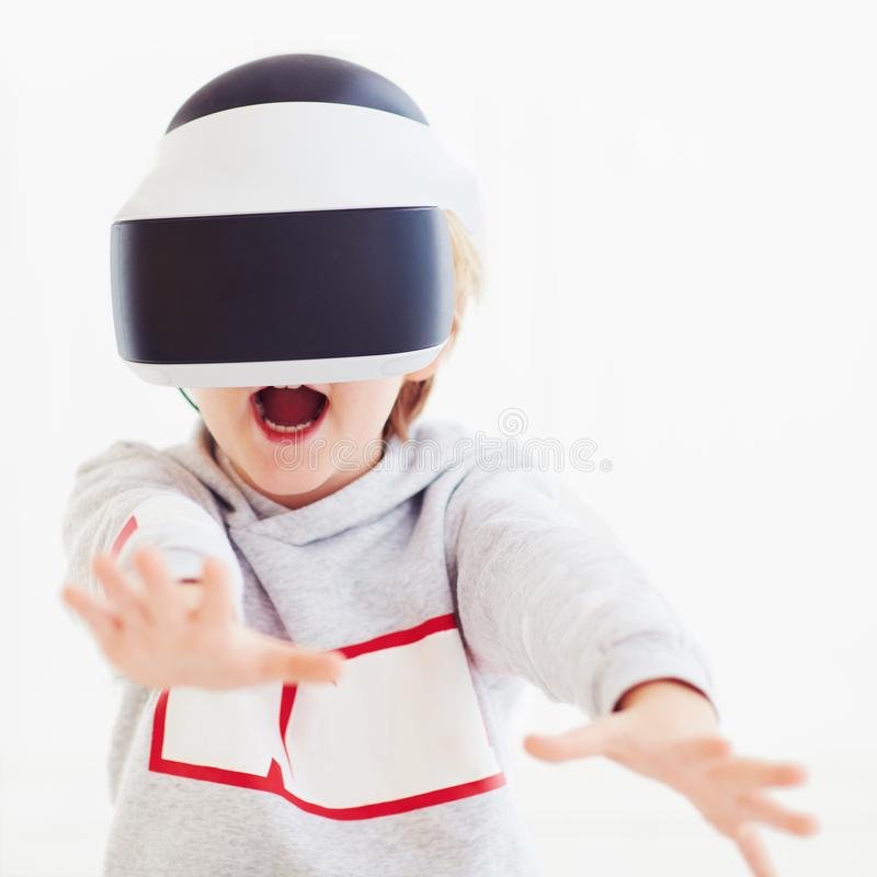 Excited young boy, kid wearing virtual reality goggles, amazed by video. Excited young boy, happy kid wearing virtual reality goggles, amazed by video royalty free stock photo