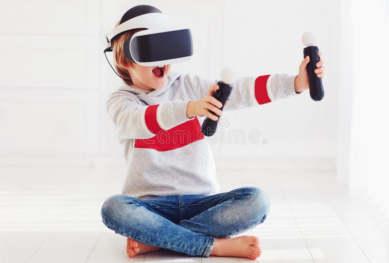 Excited young boy, kid wearing virtual reality goggles, playing in video game. Excited young boy, happy kid wearing virtual reality goggles, playing in video royalty free stock photo
