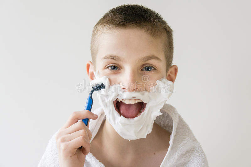 Excited Young Boy Shaving Face With Razor Stock Image