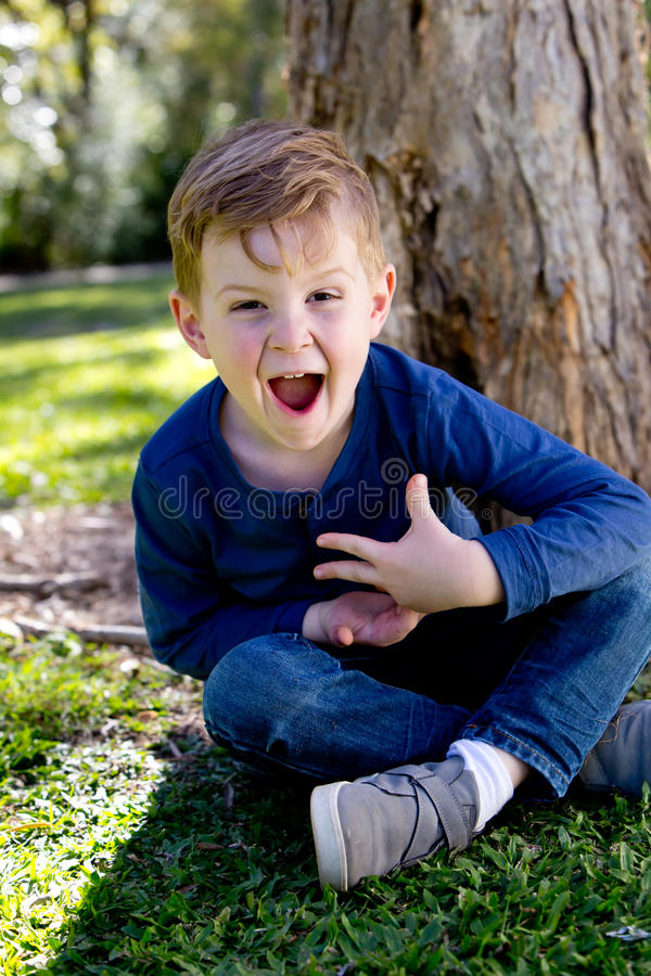 Excited young boy sitting crossed legged against tree trunk in p stock image