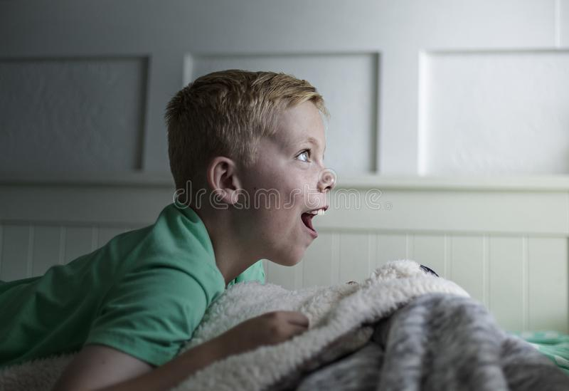 Excited young boy waking up in bed early in the morning. Side view of boy looking into the light or light coming from a window. royalty free stock image