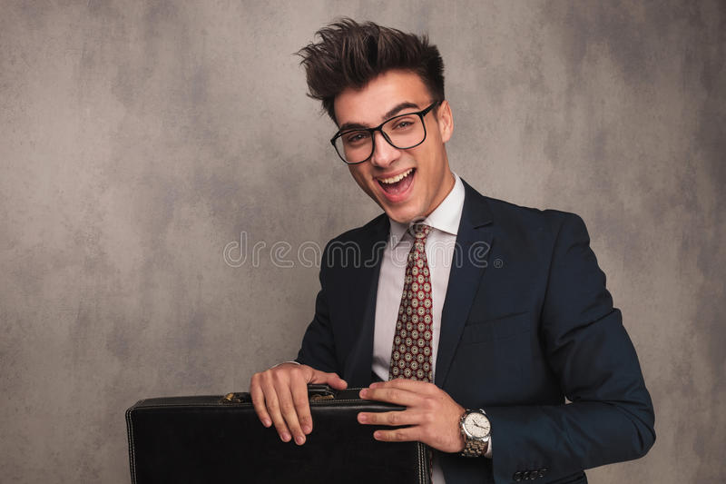 Excited young business man sitting and holding briefcase royalty free stock photography