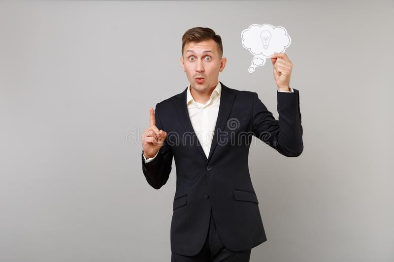 Excited young business man in suit holding say cloud with lightbulb, index finger up with great new idea isolated on. Grey background. Achievement career wealth stock photography