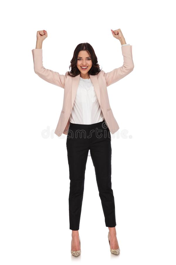 Excited young business woman with hands up and fists closed royalty free stock image