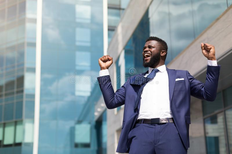Excited young businessman celebrating success and keeping hands raised standing outdoors. Copy space royalty free stock image