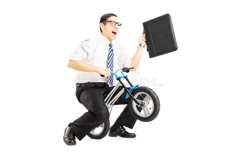 Excited young businessman with leather suitcase riding a small b royalty free stock photo