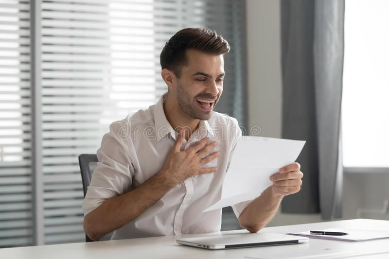 Excited young businessman received letter with unexpectedly good news. royalty free stock image