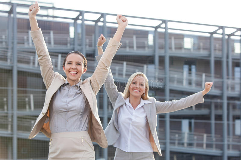 Excited young businesswomen with arms raised against office building stock image