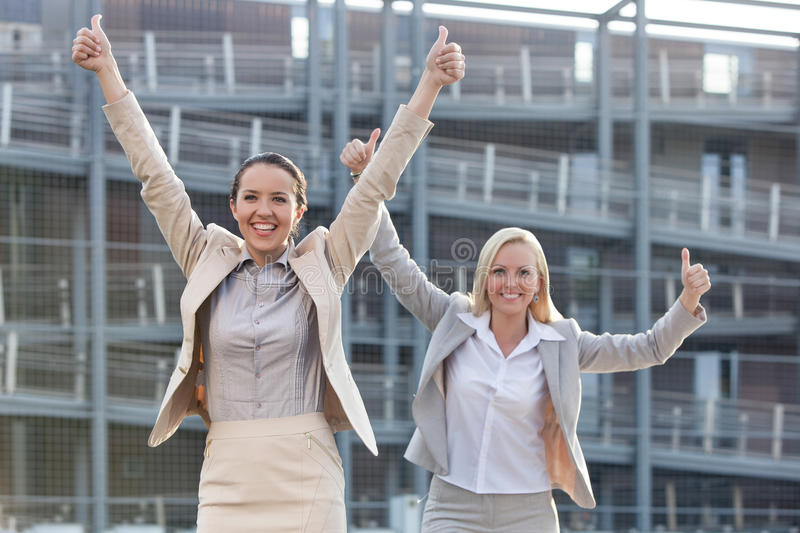 Excited young businesswomen gesturing thumbs up against office building royalty free stock photography