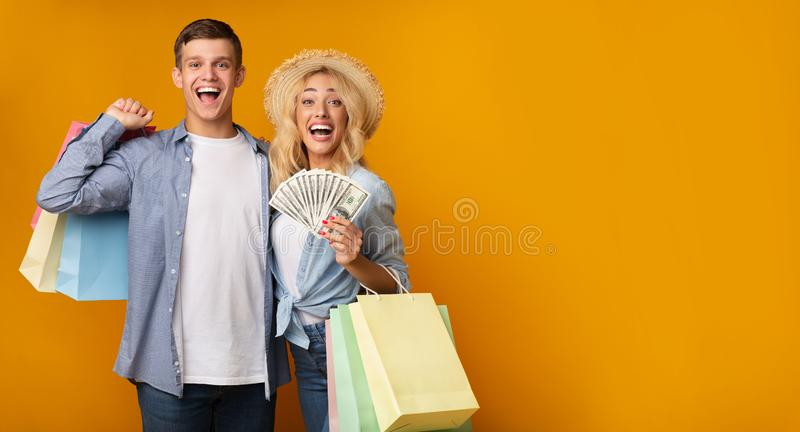 Excited Young Couple Holding Paper Bags And Bunch Of Dollars royalty free stock image