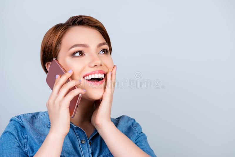 Excited young cute girl is talking on her smartphone and smiling royalty free stock images