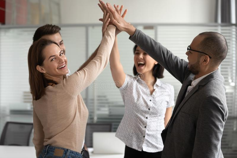 Excited young female team leader giving high five to colleagues. stock image