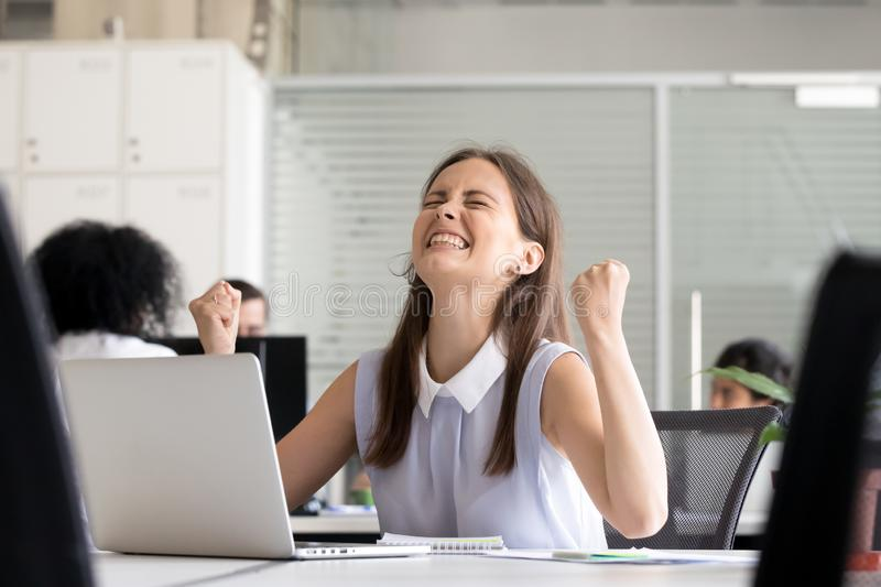 Excited young girl celebrating success achievement result. Excited young girl celebrating success business achievement result, looking up, clenching fists good stock photography