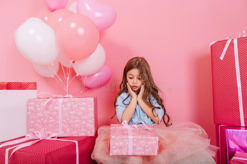 Excited young girl in tulle skirt wondering at present on knees  on pink background. Enjoying a lot of big. Presents, colorful balloons, celebrating happy stock images