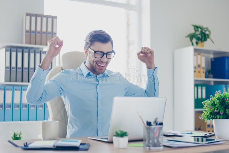 Excited young happy employer with raised hands in front of computer achieved success in his new start up or project for the first stock photography