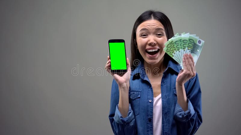 Excited young lady holding smartphone and euro banknotes, online lottery winner stock photo