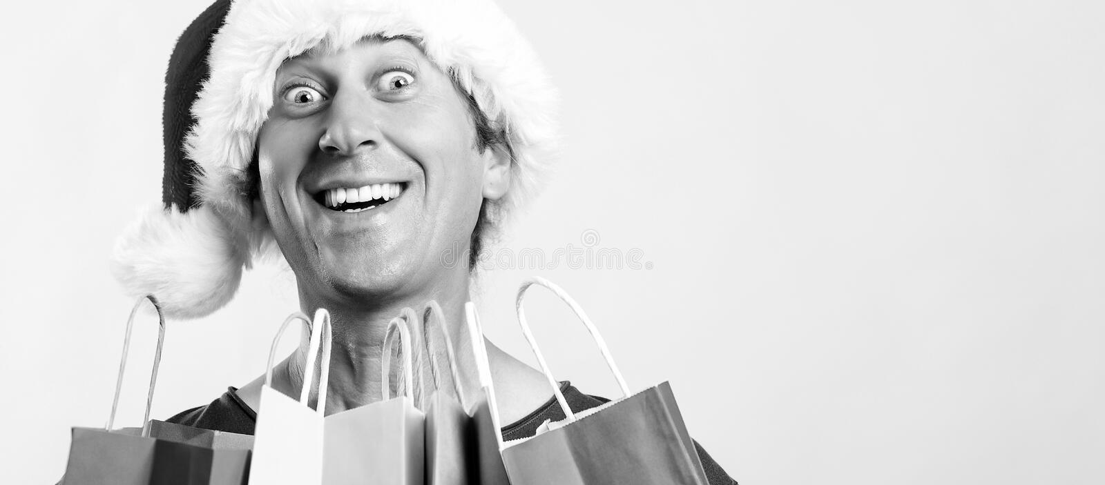 Excited young man in santa hat holding shopping bags. Christmas, sale, discount and holidays concept. Christmas crazy shopper with stock image