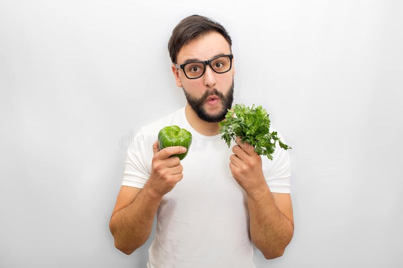 Excited young man stand in front of camera. He holds bunch of parsley and green papper in hands close to face. Young man stock photo