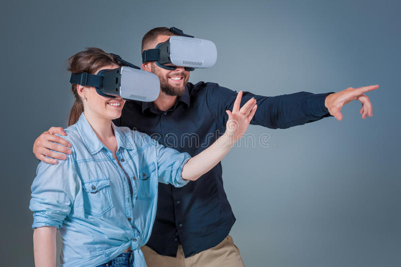 Excited young man and woman having fun with a VR glasses royalty free stock photography