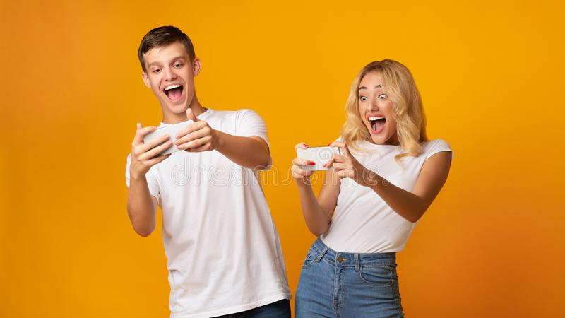 Excited young man and woman playing together on smartphones. Excited young caucasian men and women playing together and competing in video games on smartphones stock photos