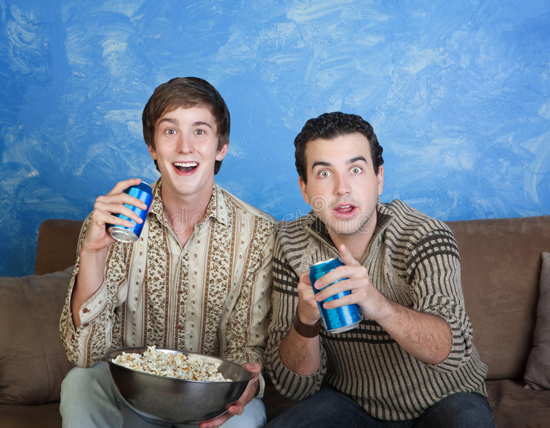 Excited Young Men. Two excited young Caucasian men with soda can and bowl of popcorn royalty free stock photography