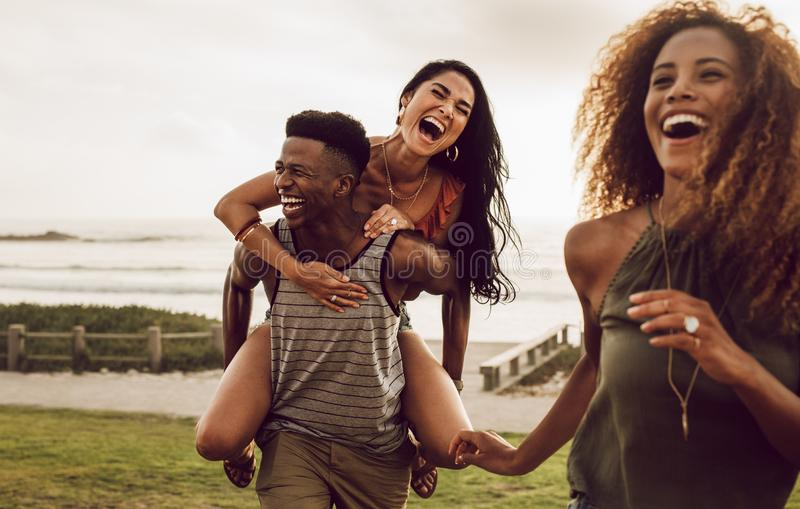 Friends enjoying on a vacation. Excited young men carrying his girlfriend on his back with female friend walking in front. Diverse group of friends enjoying on a stock photos