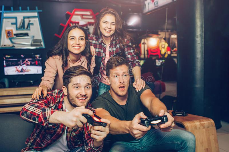 Excited young men sit on sofa in playing room. They hold joysticks and play game. Young women sit behind and cheer. People look stright forward stock image