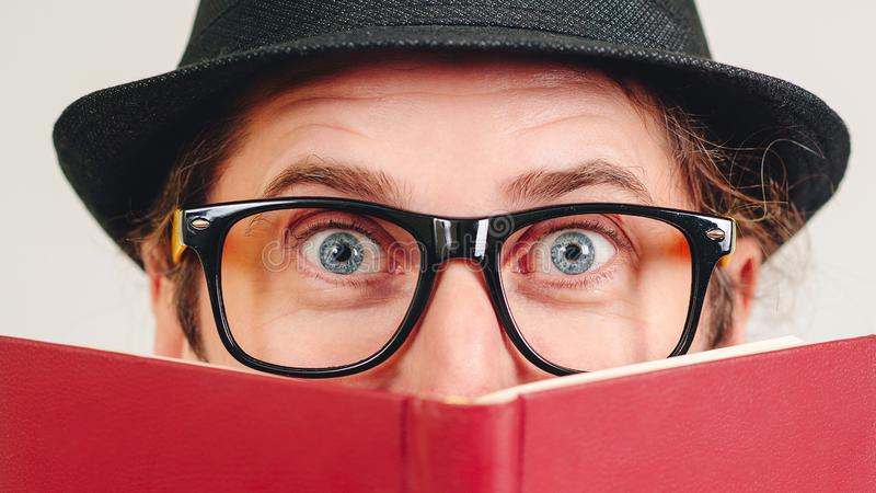 Excited young nerd guy holding book. Nerd in glasses. Funny man looking to camera. Never too late to study. Amazing man has great stock images