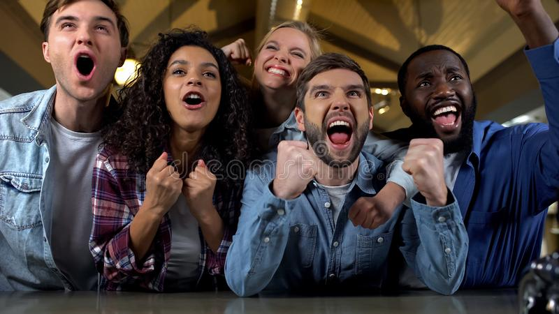 Excited young people supporting team, watching match together, rejoicing victory stock image