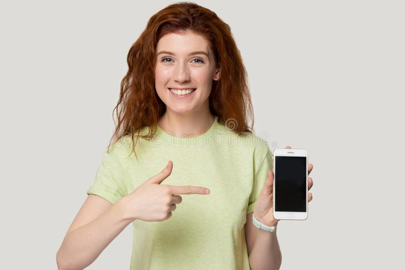 Excited young red-haired woman demonstrating new model mobile phone. royalty free stock photo