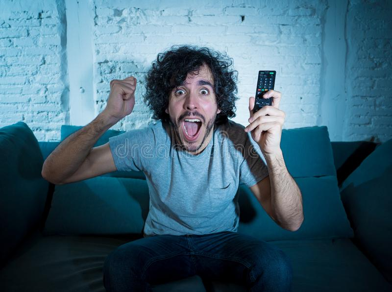 Excited young sports fan man watching soccer game on television ,celebrating goal and screaming stock photos