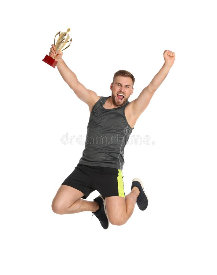 Excited young sportsman with gold trophy cup jumping on white stock photos