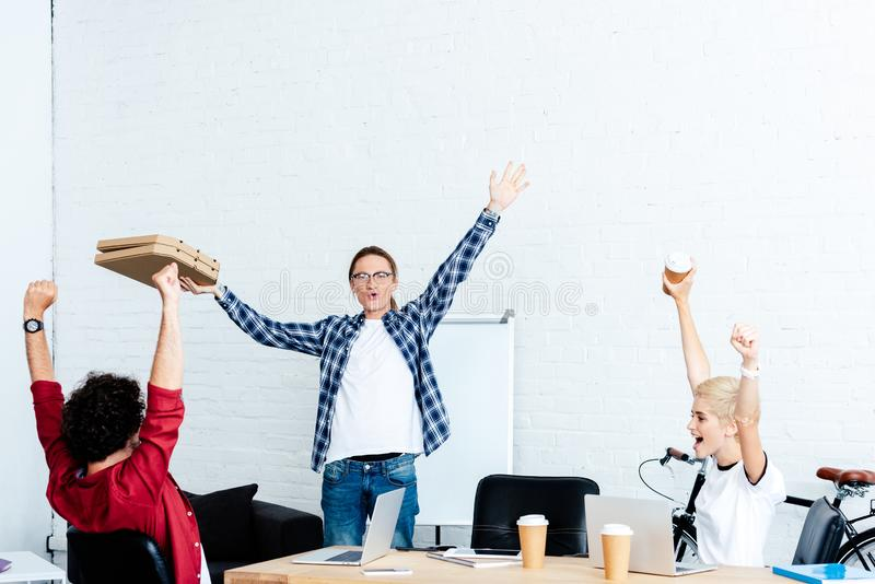 excited young start up team raising hands and looking at pizza boxes stock image